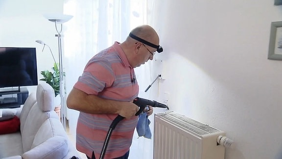 Ein Mann reinigt einen Heizkörper