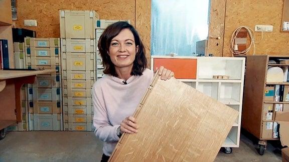 Moderatorin Janett Eger mit einem Möbelbauteil