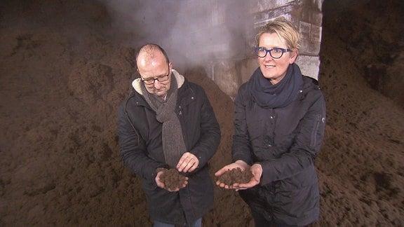 Zwei Menschen stehen in einer Kammer voller Erde und zeigen ihre mit Erde befüllten Hände vor.