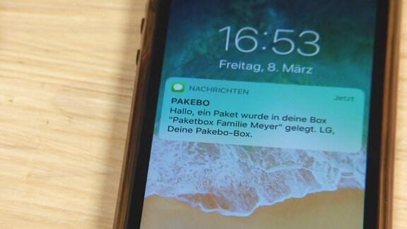 Auf einem Smartphone wird eine Nachricht auf dem Display angezeigt.