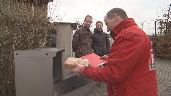 Ein Mann nimmt ein Päckchen aus dem Briefkasten.