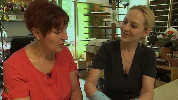 Zwei Frauen sitzen nebeneinander