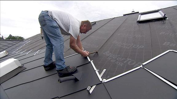 Ein Mann auf dem Dach beim Verlegen von Blechschindeln.