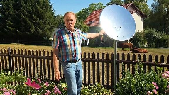Ein Mann steht neben einer verspiegelten Satellitenschüssel in einem Garten.