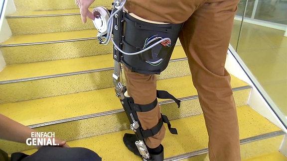 Ein Mann läuft mit einer am Bein befestigten Treppensteighilfe eine Treppe hoch.