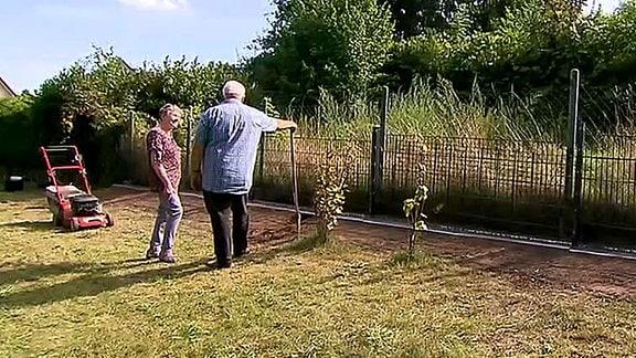Ein Mann und eine Frau stehen mit einem Spaten vor einem Zaun in einem Garten.