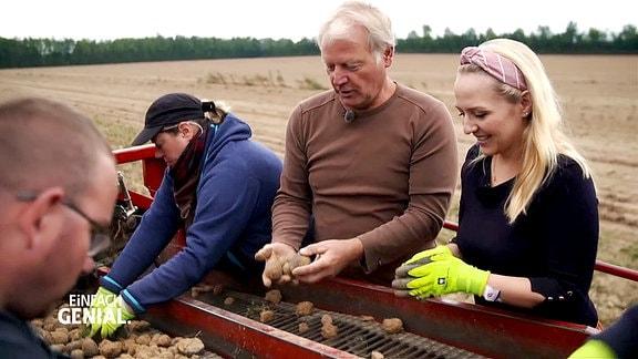 Die Moderatorin hilft beim Aussortieren der Kartoffeln.