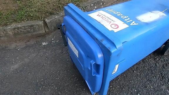 Eine umgefallene Mülltonne mit geschlossenem Deckel.
