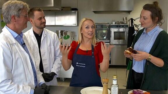 Die Moderatorin steht in einem Labor, links neben ihr stehen zwei Männer in weißen Laborkitteln, rechts neben ihr steht eine Frau, die einen Burger in der Hand hält.