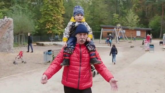 ein Mann mit einem Kind auf den Schultern