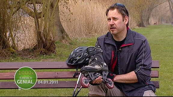Ein Mann sitzt auf einer Parkbank und hält einen umgebauten Inlineskate in der Hand.