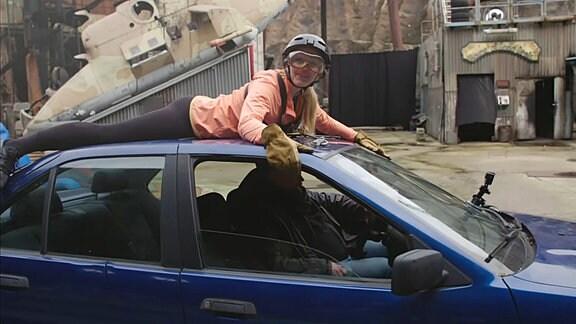 Henriette liegt auf einem Autodach.