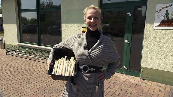 Eine Frau mit einer Kiste Spargel im Arm.