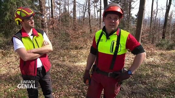 Zwei Männer in Waldarbeiter-Kleidung im Wald.