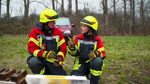 Die Moderatorin und ein Feuerwehrmann, beide in Feuerwehrausrüstung.