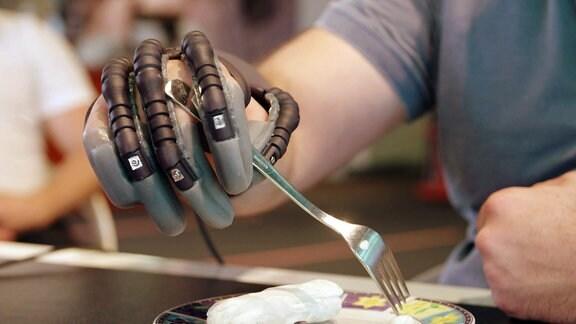 Eine künstliche bzw. bionische Hand hält eine Gabel.