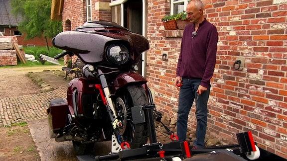 Ein Mann steht neben einer Maschine, die Motorräder bewegen kann.