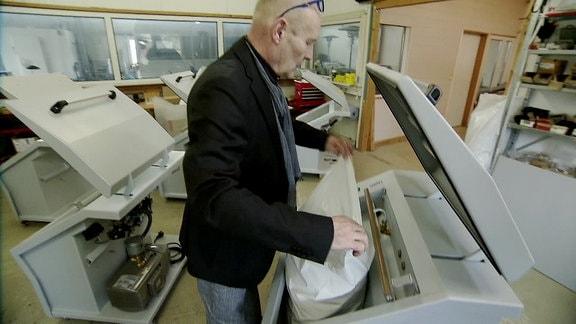 Ein Mann steckt einen Sack in eine Vakuumiermaschine.