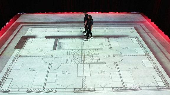 Zwei Menschen auf einer Grundriss-Projektion