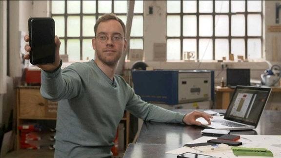 Ein Mann, der seine Erfindung der Handyhülle hochhält