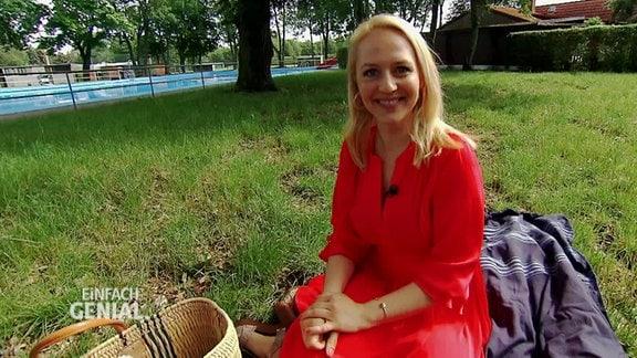 Eine Frau im roten Kleid sitzt auf einer Decke in einem Freibad.