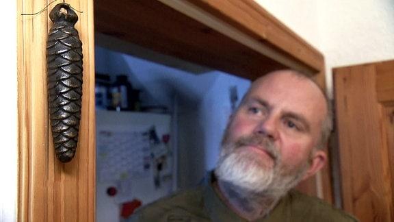 Mann betrachtet Gewicht neben Tür