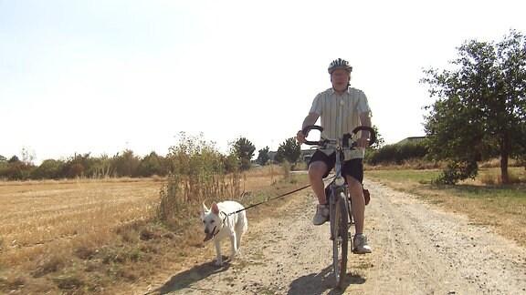 Ein Hund läuft neben einem Fahrradfahrer her.