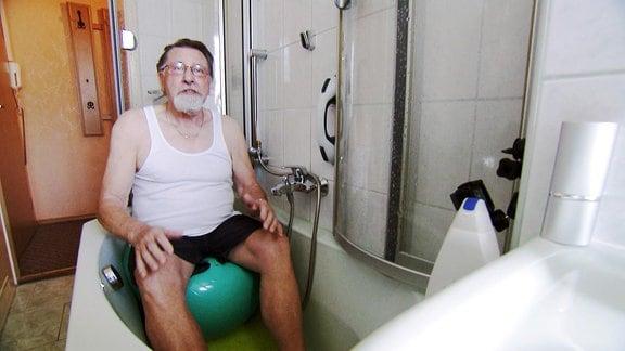 Ein Mann sitzt in einer Badewanne auf einem Gymnastikball.