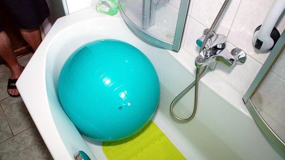 Ein Gymnastikball liegt in einer Badewanne.