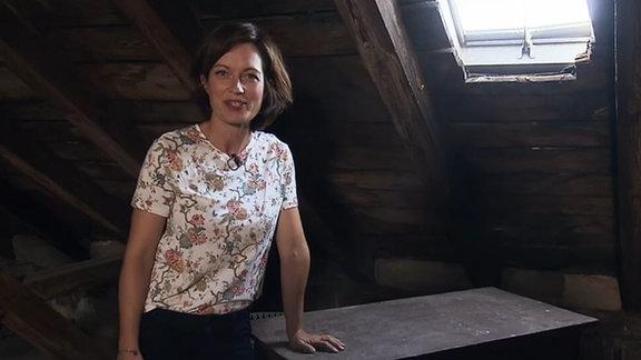 Die Moderatorin steht auf einem Dachboden.