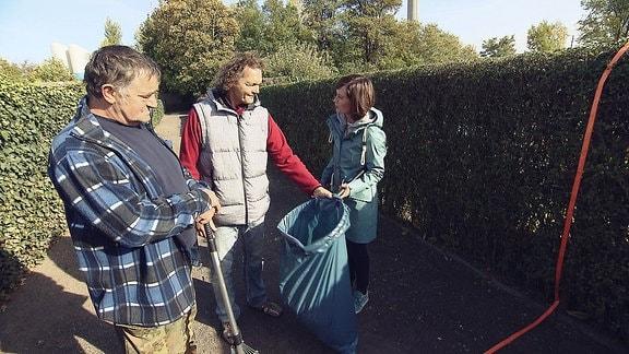 Drei Menschen stehen um eine große blaue Mülltüte herum.