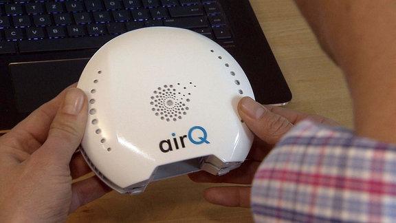 Ein Luftdruckmessgerät wird von zwei Händen gehalten.