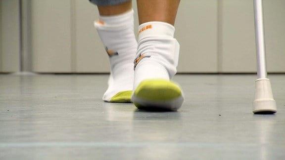 Zwei Füße beim Laufen auf dem Gang, daneben ein Gehstock.