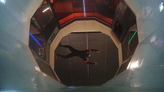 Ein Mensch schwebt in einem Windkanal.