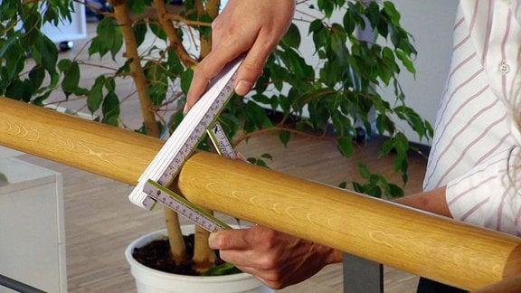 Ein Zollstock misst den Umfang von einem Holzrohr.