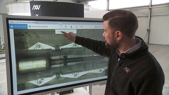 Ein Mann zeigt auf einen Monitor, der den gescannten Inhalt eines Autos zeigt.