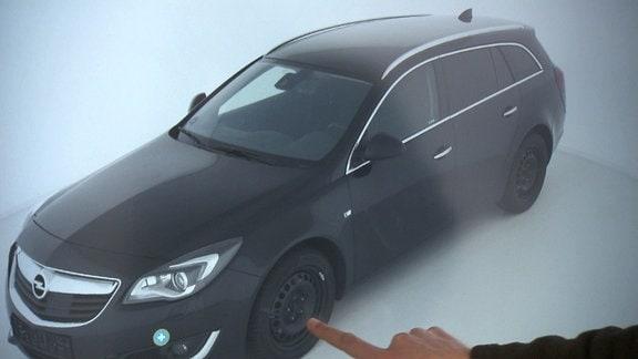 Ein Finger zeigt auf einem Monitor auf den Reifen eines Autos.