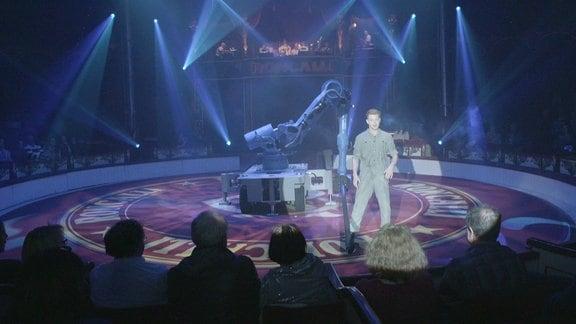 Ein Artist steht neben einem Roboter in der Manege.