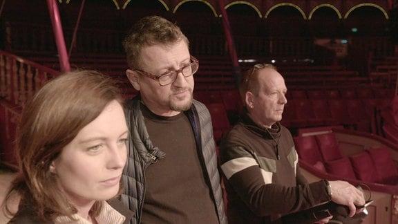 Moderatorin Janet Eger schaut mit zwei Männern in die Zirkusmanege.