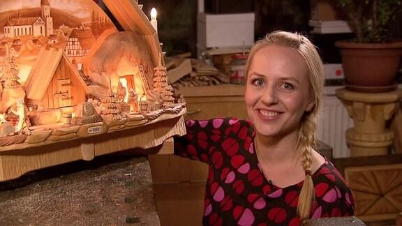 Henriette Fee Grützner hockt neben einer kunstvollen Schnitzerei und schaut lächelnd in die Kamera.