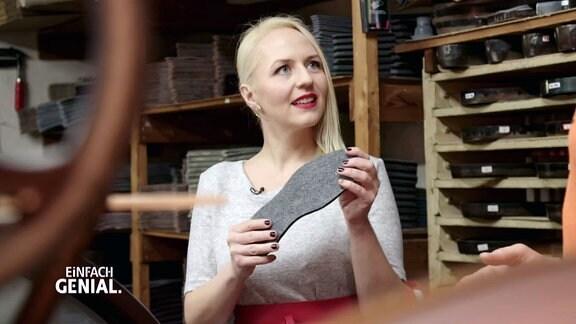 Henriette Fee Grützner hält eine Schuhsohle in der Hand.