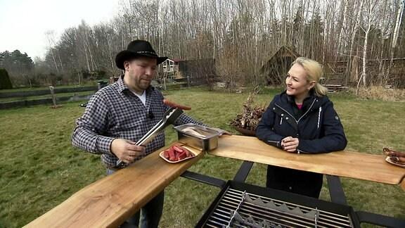 Henriette spricht mit einem Mann am Grill.