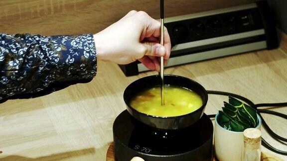Ein Heizstab wird in eine Suppenschüssel gehalten.