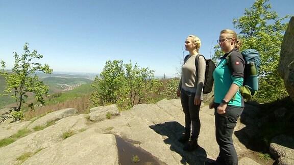 Zwei Frau stehen an einem Aussichtspunkt auf einem Berg und bewundern die Aussicht.