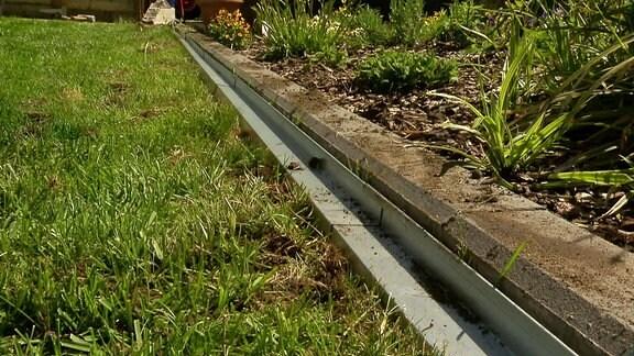 Metallbleche mit Steckverbindung bilden eine Rasenkante.