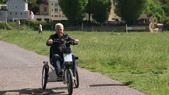 Mann fährt E-Dreirad