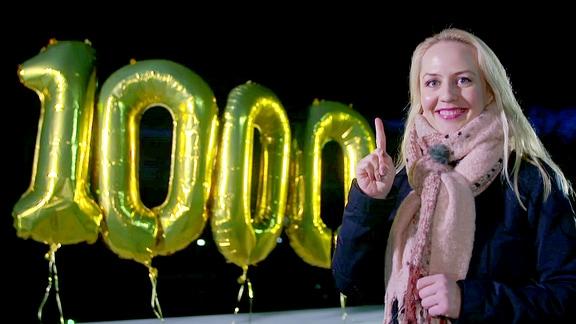 Henriette Fee Grützner mit einer 1000 aus goldfarbenen Ballon