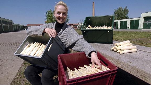 Frau hält Kisten mit Spargel