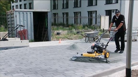 Ein Mann schiebt eine Pflasterkehrmaschine über frisch gelegtes Pflaster.
