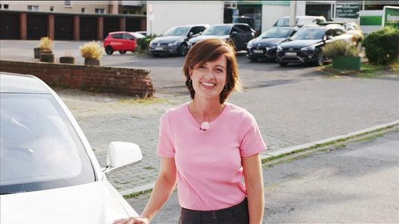 Moderatorin Janett vor einem autonomen Fahrzeug.